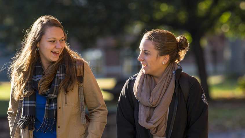 two student wearing jackets and scarves walking and talking outside.