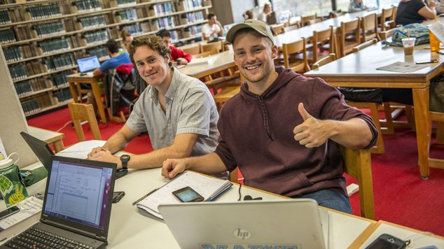 two guys with computers in library smiling, one giving a thumbs up