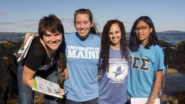 four students smiling and holding schoolwork by the ocean