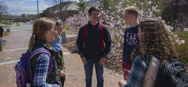 five students standing with backpacks on by flowering tree
