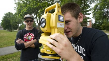 student looking through surveying equipment