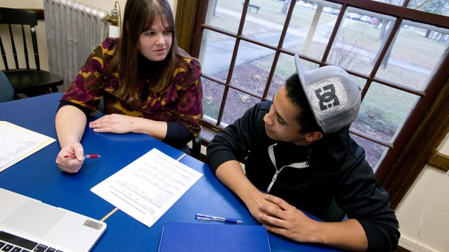 student and staff-person going over paperwork