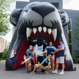 Orientation Volunteers posing in front of inflatable UMaine bear