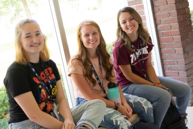 3 students sitting on a bench indoors at orientation