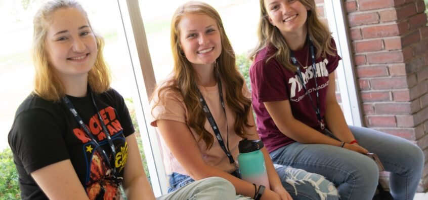 3 female students sitting on a bench indoors at orientation