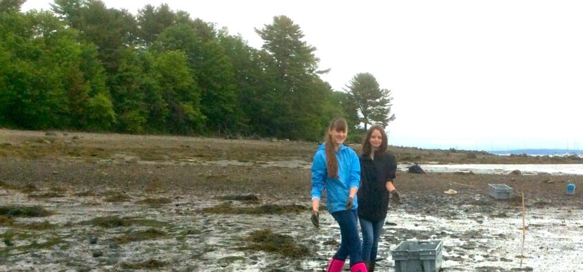 2 students standing in the mud, collecting samples at the coast for a STEM course.
