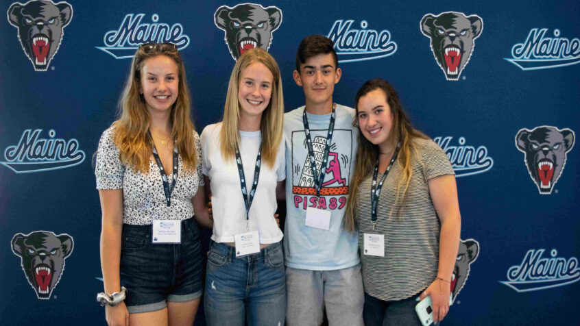Four students from Orientation standing in front of a UMaine banner