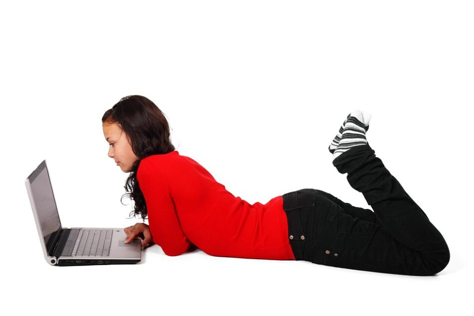 Student lying on stomach, looking at a laptop