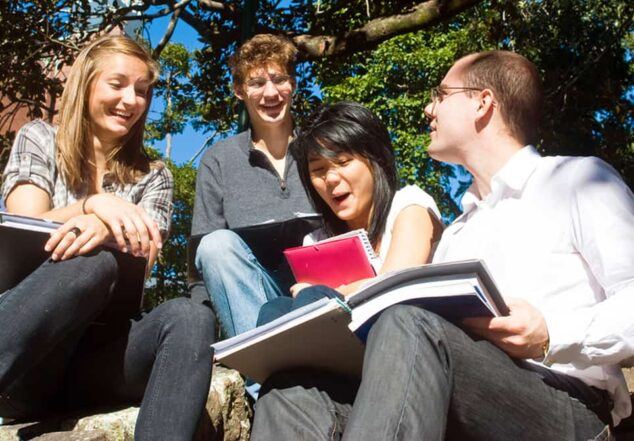 Four happy students under a tree looking at books