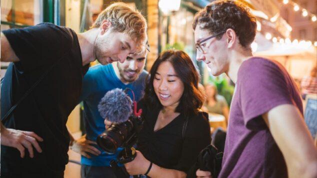 Students and professor looking at a camera