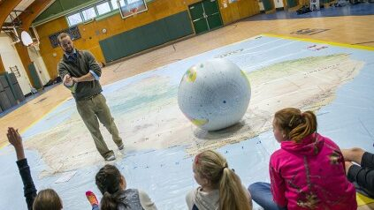 instructor teaching children in gym with giant map