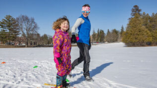 instructor teaching child to ski