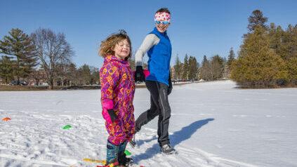 instructor teaching child to ski