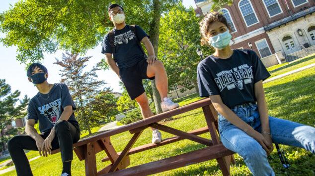 Students at UM sitting at a picnic table wearing masks