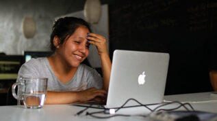 Person sitting at laptop smiling with hand on head