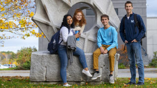 four students in front of sculpture on UMaine campus