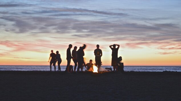 students on a beach at sunset gathered around a campfire
