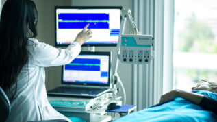 medical professional back to pointing at monitor as patient lays in bed