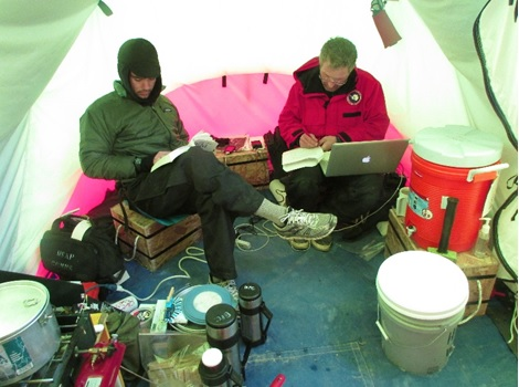 Figure 3: A view inside our cook tent; the University of Washington's graduate student, Trevor, is on the left, and Dr. John Stone is on the right. In case you were wondering – no, we did not have WiFi at our field sites! Dr. Stone is transferring photos from his camera onto the computer.