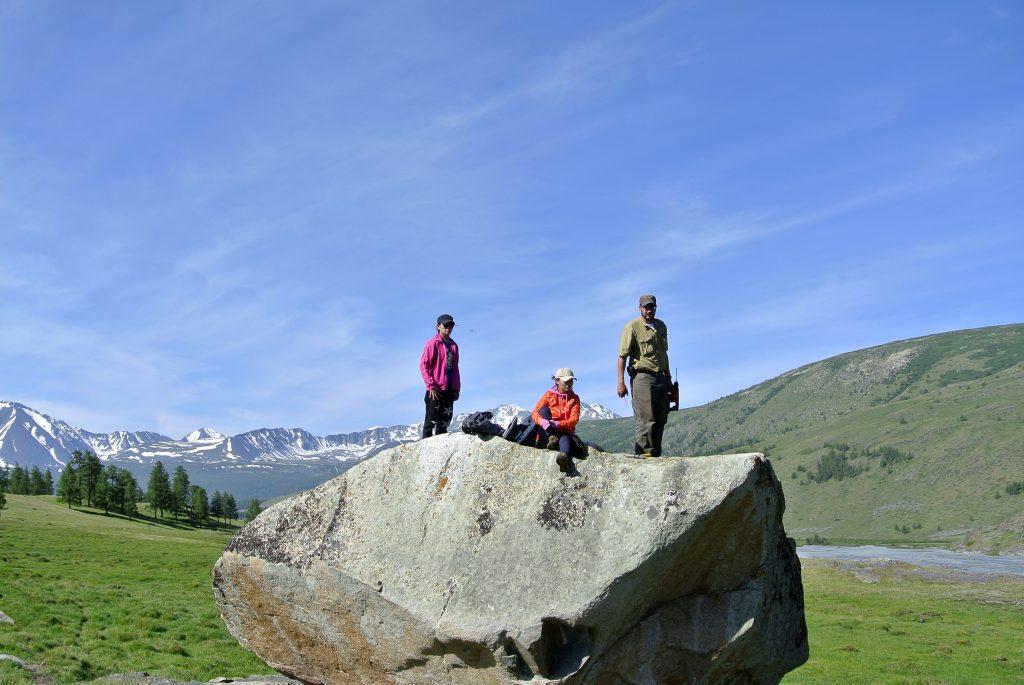 Caleb Ward, Tsetse, and Pagma sampling a granite boulder