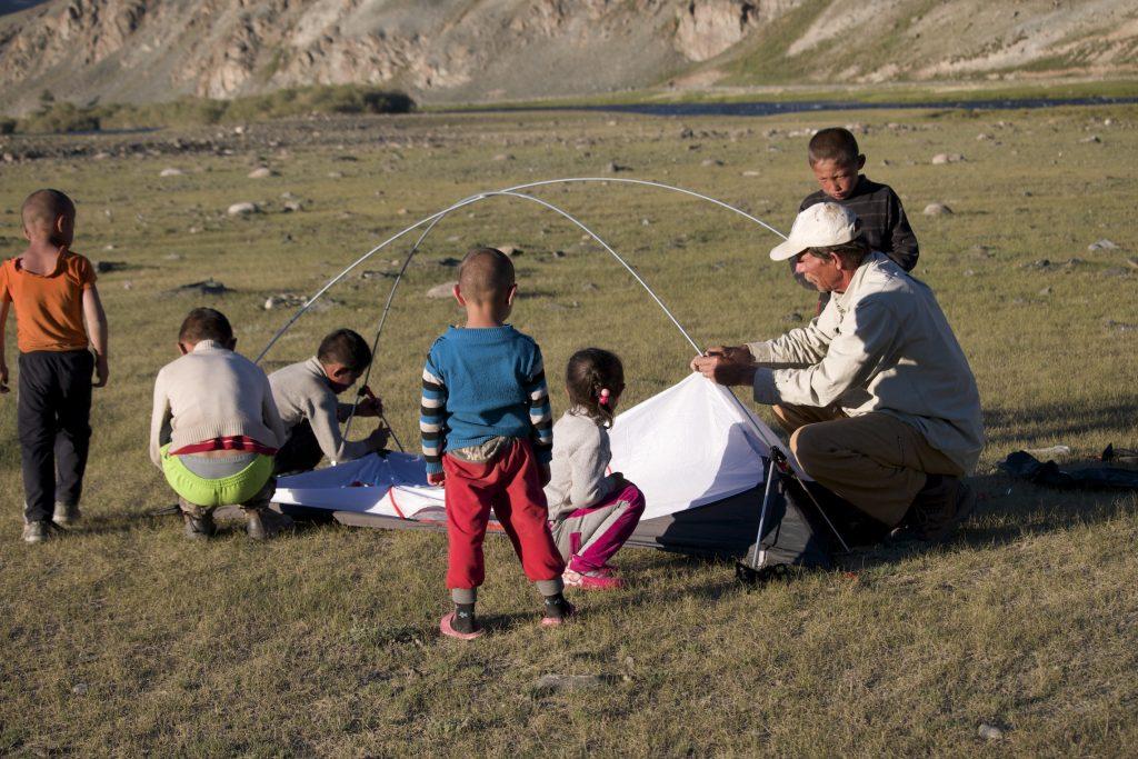 Young Khazak children help Dave Putnam set up his tent