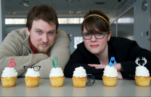 Two people posing with cupcakes