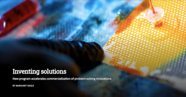 A black-gloved finger points at a square of white paper that appears to have yellow, green and blue mesh covering it. Two items that look like suction cups with red wires coming out of the tops are attached atop the mesh. This image is scientific and abstract. Text at the bottom right of the image reads: Inventing Solutions: New program accelerates commercialization of problem solving innovations, by Margaret Nagle.