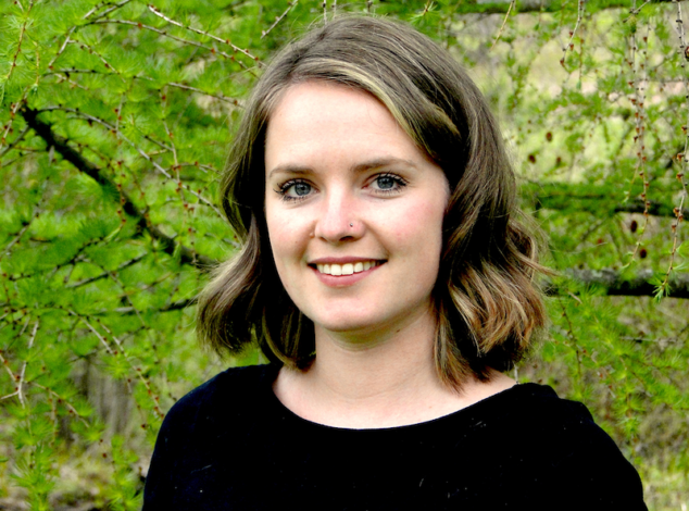 A headshot of a young woman in a black blouse standing in front of green tree branches