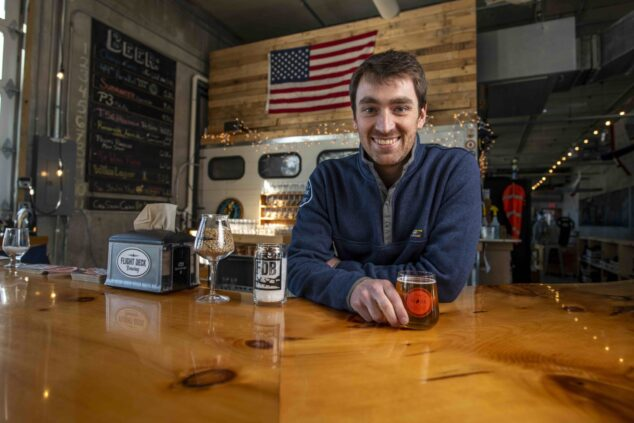 Nate Wildes standing behind the polished wood bar at Flight Deck Brewing in Brunswick, Maine.
