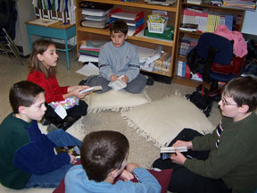 Students conduct a word activity while seated in a circle on the floor