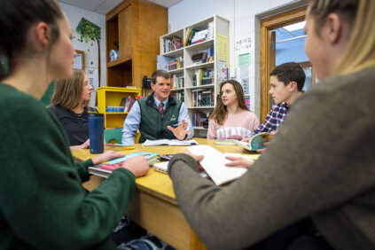A school administrator sits at a table in a classroom surrounded by students and teachers.