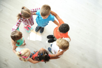 Little children making circle with hands around each other