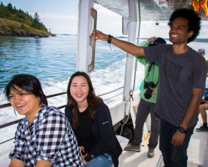 Three Graduate students taking a boat ride out to see Cook Aquaculture's Salmon Pens