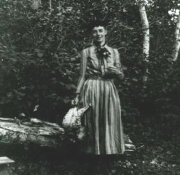 P00342 Fannie P. Hardy (Eckstorm) standing in the woods holding one or more dead grouse.