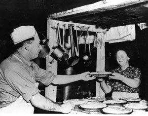 P00929 Blaine 'Tinker' Averill, the cook, and his wife, Goldie, taken between 1945 and 1947, at Little Musquash Lake Woods camp. These two worked together to feed the lumbermen at this camp, three meals a day, all winter, for fifteen years. Goldie remembers that 'I used to love to cook. My husband and I did everything together. And now I just hate to get a meal for myself... He'd do the mixing, and I'd do the frying. We did everything together. And the pies, he'd fill them, and I'd put the meringue on top. [NA1075.006]