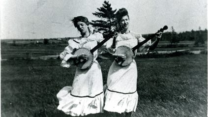 Addie Weed and Blye Spencer of Veazie, Maine in white dresses standing in a field playing banjos and singing.