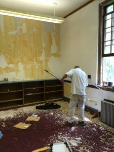 Facilities worker priming walls of former archive room.