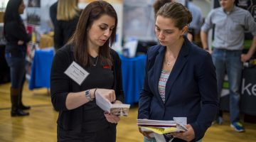Two woman looking over a career fair brochure.