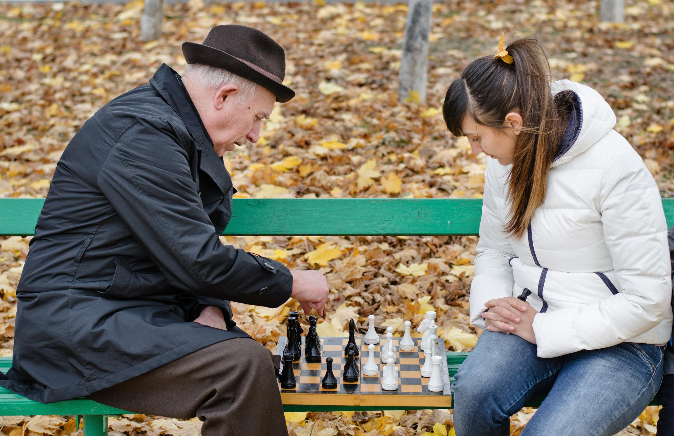 Elderly gentleman playing checkers with young woman