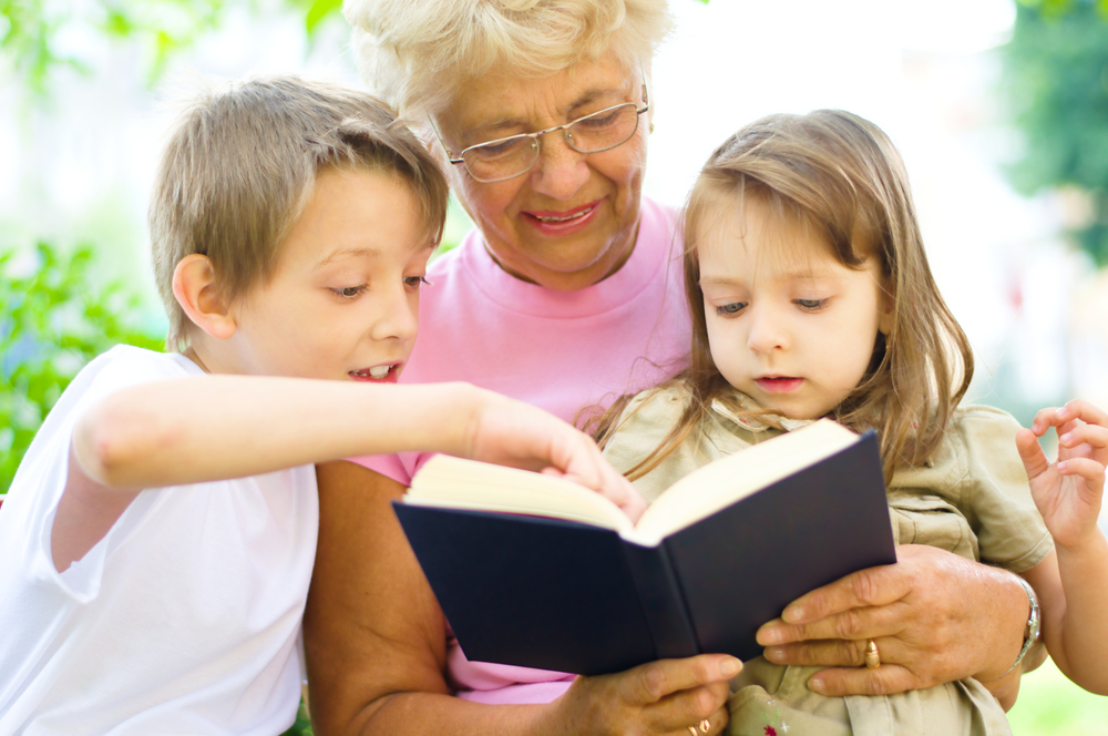 Elderly woman reading to children