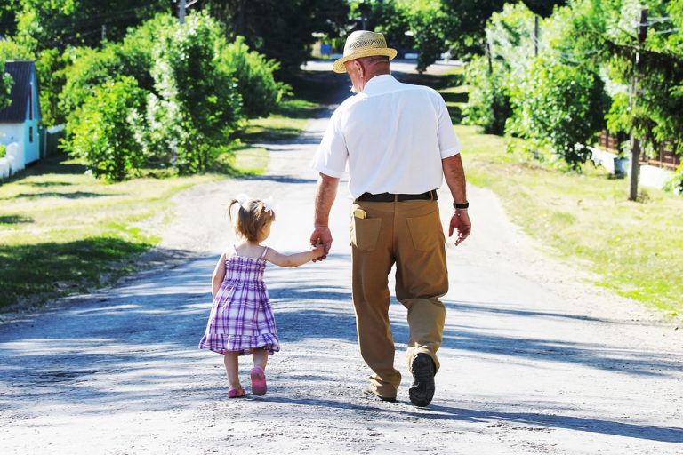 Elderly man walking with small child