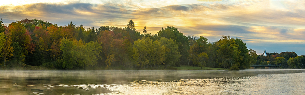 photo of river with autumn trees and colorful sky