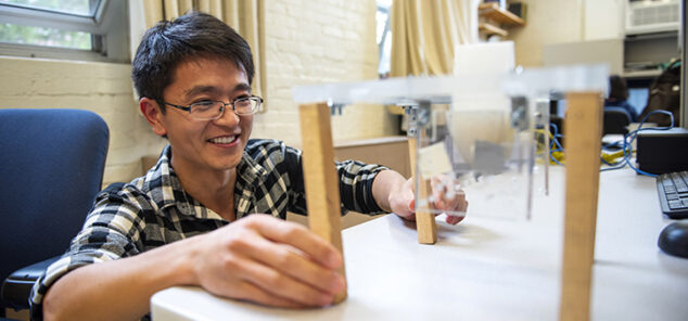 student building a small structure on desk