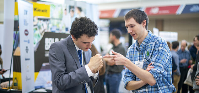 two men talking to each other at a job fair