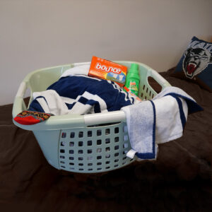 full laundry basket on student bed