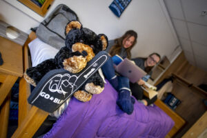 York double room with female students, blurred in background with foam spirit finger and black bear in focus