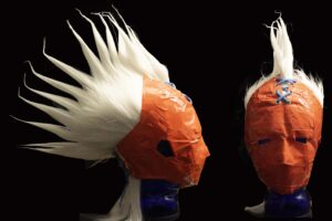 This image depicts a mask which covers nearly the entire head except for an open palm sized hole on the crown of the head. The mask is made almost entirely of orange duck tape. From the hole left in the back of the mask an explosion of white hair stylized to look like a mohawk emerges from the mask. The mask is held in place with blue shoe laces that tie in place in two locations, one above the forehead and the other in the back of the head atop of the neck. The mask gives a very claustrophobic feeling since there is a minimal amount of opening for the eyes, nose and ears.