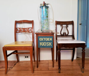"""An 18"""" tall glass cylinder with a wooden lid. Attached to the lid is a small oxygen tank which hangs inside the glass. The valve apparatus that accesses oxygen is situated above the lid. There is an oxygen mask attached to one of the nozzles on the apparatus with plastic tubing. The entire assembly sits on a small wooden table bearing a sign on a wooden panel which says """"Oxygen Kiosk"""" in yellow stenciled letters on a deep green background. On either side of the """"Oxygen Kiosk"""" sits two wooden chairs."""