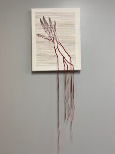 Full piece, x-ray of hand with embroidery representing veins, and running off the frame.