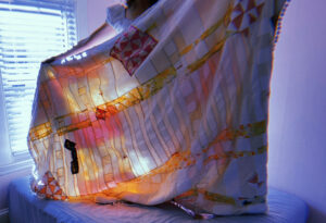 Artist stand holding white, pink and yellow quilt in front of her. Light streams through the window.
